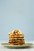 A stack of pancakes topped with banana slices and with dripping maple syrup