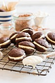 Chocolate whoopie pies filled with cream on a wire rack