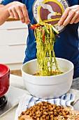 A man serving vegan vegetable spaghetti with pesto