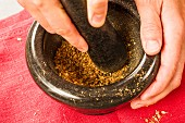Roasted coriander seeds being crushed in a mortar