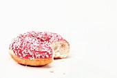 A pink doughnut, bitten