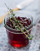 A jar of cherry jelly with thyme
