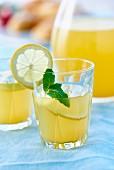 Limonade im Glas mit Zitronenscheibe und Minze