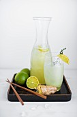Ginger and lime soda with ingredients on a varnished tray