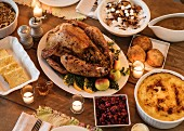 A table laid with roast turkey and side dishes for Thanksgiving