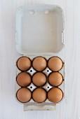 Neun braune Eier im Eierkarton (Draufsicht)