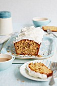 Walnut loaf cake with frosting a grated coconut, sliced