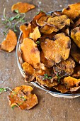 A pile of sweet potato crisps with fresh thyme and salt