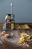 A pasta machine with fresh pasta dough and homemade tagliatelle