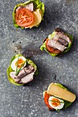 Open sandwiches with cheese, meat, eggs and tomatoes