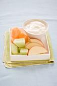 Melonenstücke & Apfelschnitze mit Joghurt im Schälchen