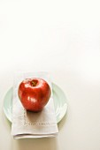 A red apple on a fabric napkin on a plate