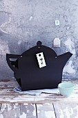 A teapot cut out of black construction paper as gift wrap for a cake