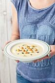 Frau hält einen Teller Sellerie-Kartoffel-Cremesuppe mit Meerrettich