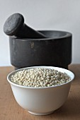Sorghum in a porcelain bowl in front of a mortar