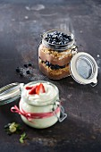 A jar of chocolate mousse with crumbles and blueberries and a jar of white mousse