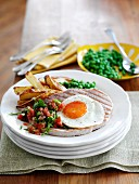 Grilled ham with chips, peas and fried egg