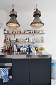 Vintage Pendelleuchten im Industriestil über moderner Küchentheke mit Edelstahlplatte und schwarzer Unterschrankfront, an Wand minimalistische Ablagen mit Geschirr