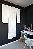 Von Decke abgehängte Stange mit edlem Kimono in Weiß vor schwarz getönter Wand, seitlich schlichter Arbeitsplatz