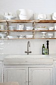 Rustic sink on kitchen counter below white crockery on rusty shelves