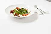 Mozzarella and tomato salad with olives, balsamic vinegar and a pesto dressing