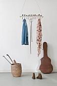 Abgehängte Holzstange mit durchgesteckten, gebogenen Vintage-Löffeln als Kleiderhaken, darunter nostlagischer Gitarrenkoffer und Korb mit Hockeyschläger