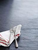 Geschirrtuch und zwei Gabeln auf Schieferplatte