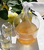 Homemade quince liqueur in a bulbous bottle with a fabric stopper