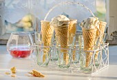 Homemade ice cream in cones in a cone holder in front of a kitchen window
