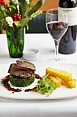 Roast lamb on a spinach timable with polenta sticks and blackcurrant jus