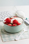 Melon balls with yoghurt and mint on a desk