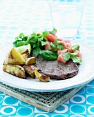 Roasted veal chop with roast potatoes served with a watermelon and avocado salad with coriander