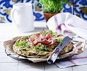 A rustic pizza with mozzarella, Gorgonzola, Parma ham and parsley