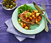 A pork chop with root vegetables and pineapples