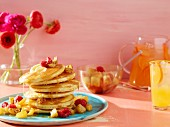 A stack of pancakes with fruit, fruit juice and flowers