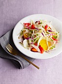 Raw vegetable salad on a plate with a fork