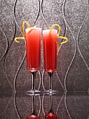 Two red cocktails with lemon spirals on a reflective surface
