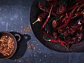 Getrocknete Chilischoten und Chiliflocken in Schalen (Draufsicht)