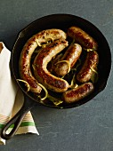 Fried sausages with onions in cast iron pan