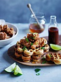 Spicy cornmeal waffles with popcorn chicken, honey and hot sauce