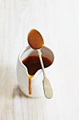 Caramel sauce in a white porcelain jug with a spoon