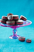 Grey macarons with a red fondant filling on a cake stand