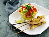 Chicken skewers with curry served with a mango and pepper salad with coriander