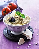 Hummus with olives, lemon and mint leaves