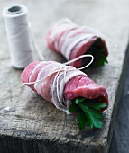 Raw beef roulade wrapped in bacon and filled with parsley