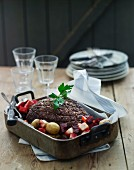 Roast lamb with beetroot and potatoes in a roasting tin