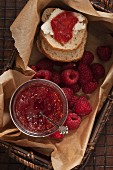 Homemade raspberry and mango jam in a basket with slices of bread and fresh raspberries