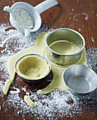 Raw shortcrust pastry in baking tins and cutters on a floured work surface