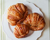 Three croissants on a plate (seen from above)