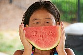 A little girl eating a seedless watermelon at a pool party